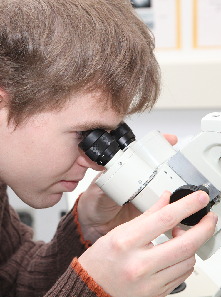 SUNY Poly student looks into a microscope