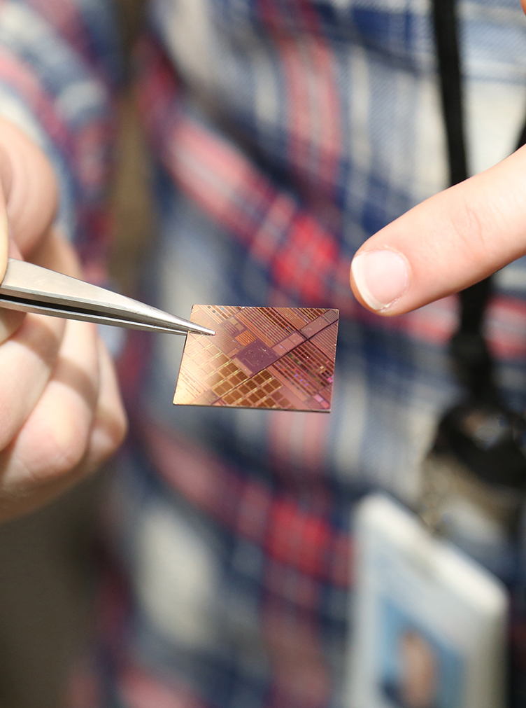 Graduate student holds and point to a silicon chip