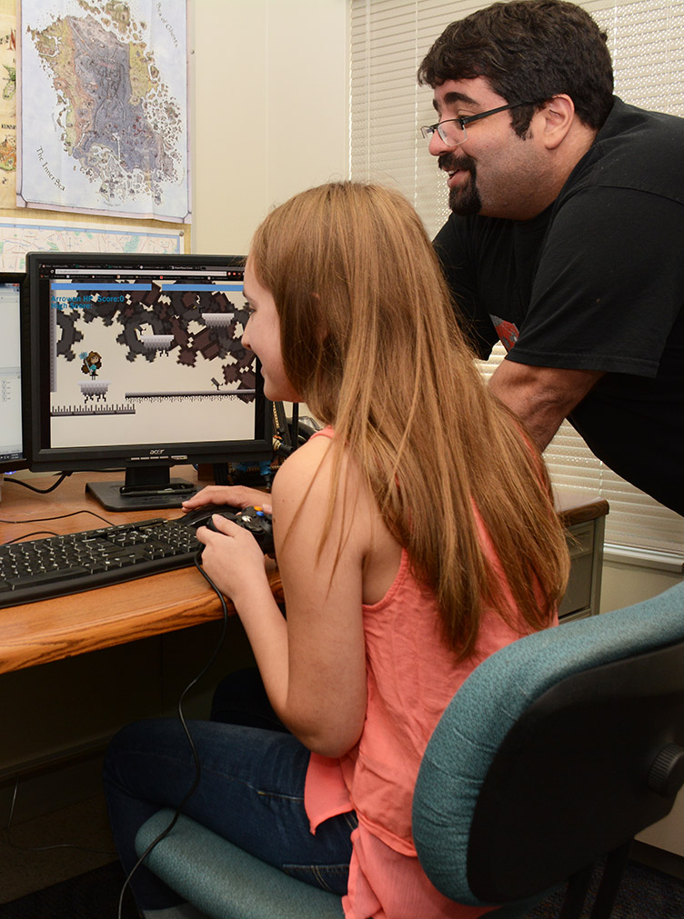 Professor Ib Yucel works with a student on her game design.