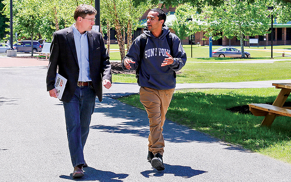 Professor John Marsh walks with student
