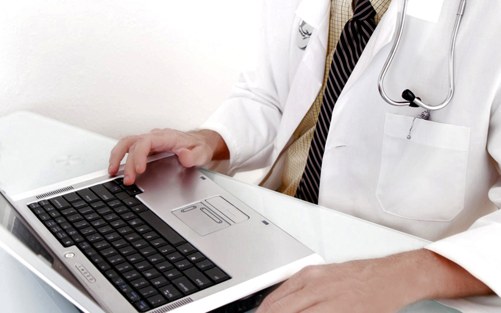 MS in FNP - illustrative photo of person in lab coat using laptop