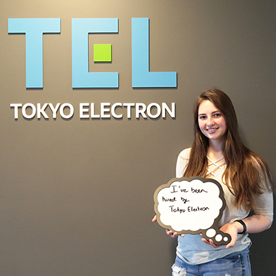 Student standing in front of Tokyo Electron sign