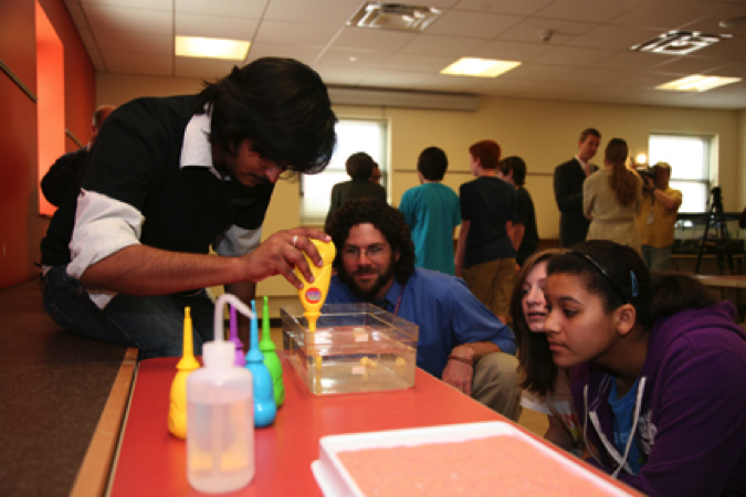 Graduate Student does science experiments with area high school students