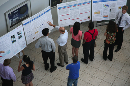 Faculty and student view posters at the poster presentation