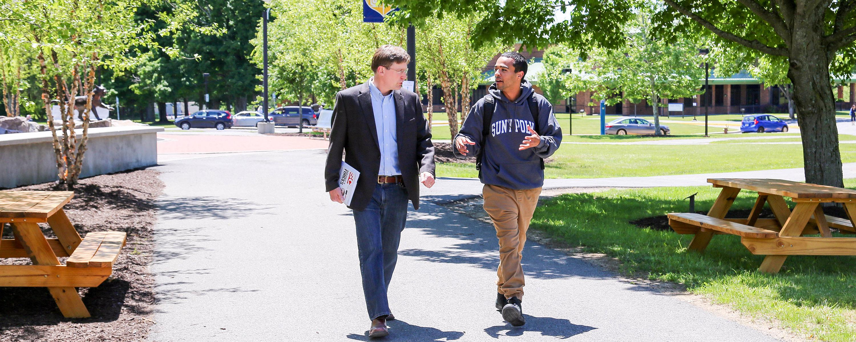 Student and Professor walking on Utica Campus